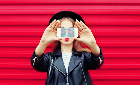 Fashion glamour woman makes self portrait on smartphone blowing lips over city pink background Standard-Bild