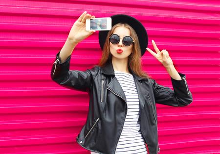 Mode mooie vrouw maakt zelfportret op smartphone in zwarte rots stijl over de stad roze achtergrond