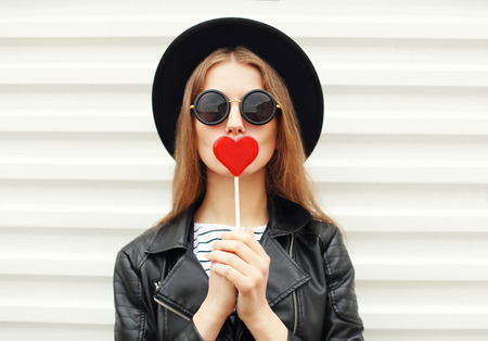 Fashion sweet woman having fun with lollipop over white background