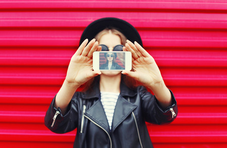 Fashion woman makes self portrait on smartphone over city pink background