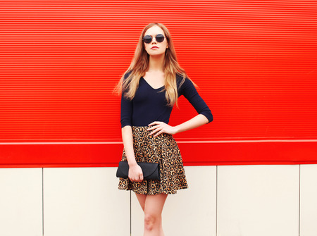 Fashion beautiful woman in leopard skirt sunglasses handbag clutch posing over red colorful background