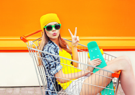 Fashion pretty cool girl in shopping trolley cart with skateboard over colorful orange background Stock Photo