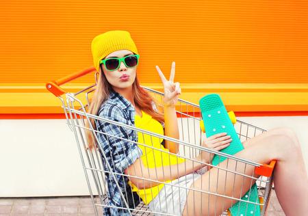 Fashion pretty cool meisje in winkelwagentje kar met skateboard over kleurrijke oranje achtergrond Stockfoto