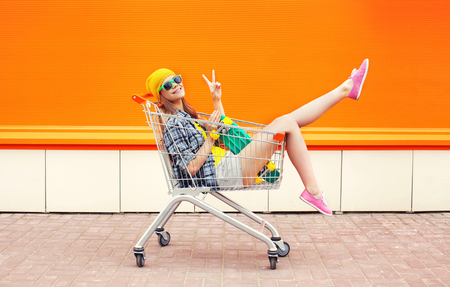 Fashion pretty cool girl in trolley cart having fun over colorful orange background
