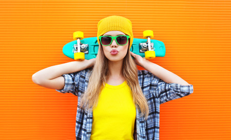 Fashion pretty cool girl with skateboard over colorful orange background Stok Fotoğraf