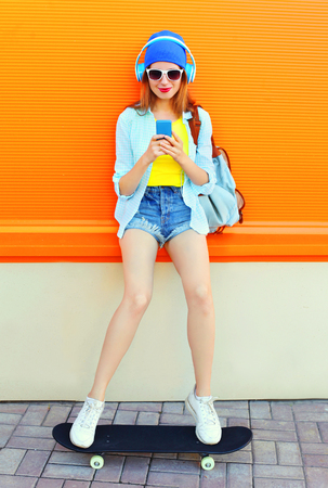 Fashion pretty cool girl listens to music using smartphone on skateboard over colorful orange background Stok Fotoğraf - 62347458