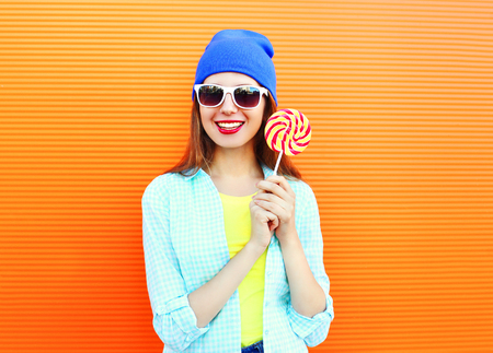 sweettooth: Portrait pretty cool smiling woman and lollipop over colorful orange background