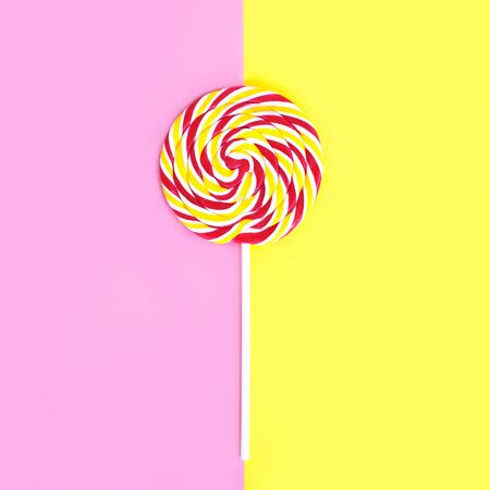 sweettooth: Colorful lollipop caramel on stick over pink yellow background top view
