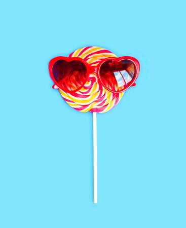 sweettooth: Colorful lollipop caramel on stick with sunglasses over blue background top view