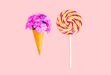 sweettooth: Ice cream cone flowers and colorful lollipop caramel on stick over pink background top view