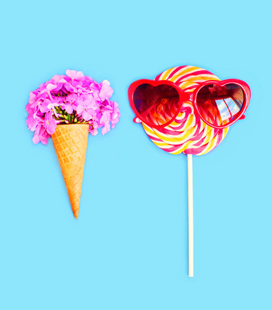sweettooth: Ice cream cone flowers and colorful lollipop caramel with sunglasses on stick over pink background