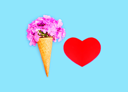 red color: Ice cream cone with flowers and red heart shape over blue colorful background top view Stock Photo