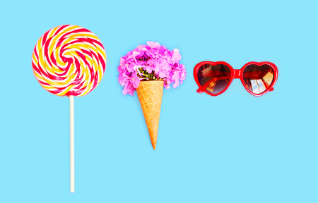 sweettooth: Ice cream cone with flowers sunglasses heart shape lollipop caramel on stick over blue background top view
