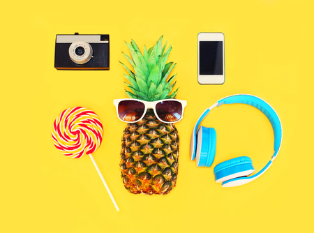 Pineapple with sunglasses headphones lollipop vintage camera smartphone over colorful yellow background Stok Fotoğraf