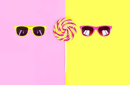 sweettooth: Two sunglasses and colorful lollipop caramel on stick over pink yellow background top view