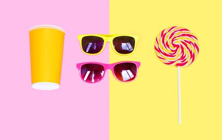 sweettooth: Two sunglasses and colorful lollipop caramel on stick with cup juice over pink yellow background top view