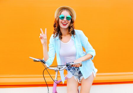 Mode hübsche Frau mit dem Fahrrad über bunten orange Hintergrund