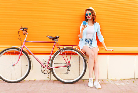 Pretty cool smiling young woman using smartphone with retro bicycle over colorful orange background