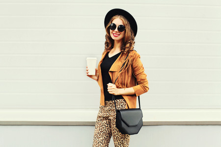 Fashion happy young smiling woman with coffee cup wearing a retro elegant hat, sunglasses, brown jacket and black handbag over grey background Stok Fotoğraf