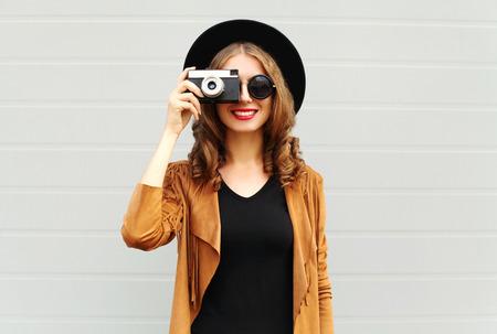 De manier kijkt, vrij koel jong vrouwenmodel met retro filmcamera die een elegante hoed, bruin jasje, krullend haar in openlucht over stads grijze achtergrond dragen