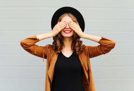 closes eyes: Fashion pretty cool young woman closes eyes cute smiling wearing a vintage elegant hat brown jacket playing having fun over grey background