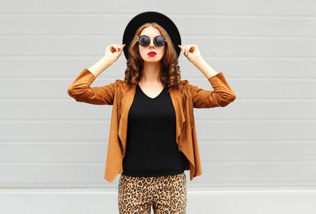 Fashion pretty woman wearing a black hat, sunglasses and jacket over urban grey background Standard-Bild