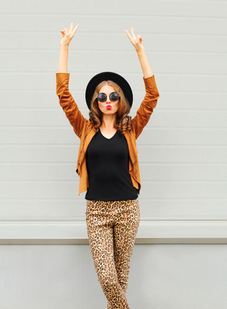Fashion pretty young woman wearing a black hat, sunglasses and jacket raises hands up over urban grey background