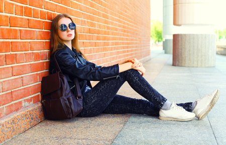 Fashion young woman in black rock style sitting over bricks background Banque d'images