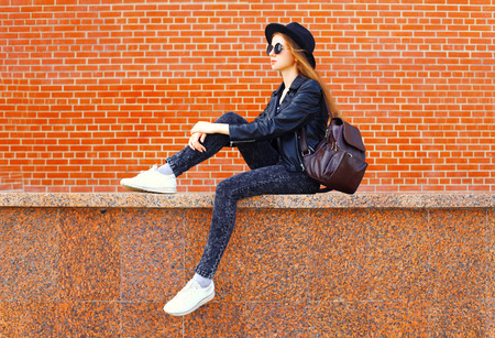 Fashion young woman wearing a black rock style sitting over bricks wall background in profile Banque d'images