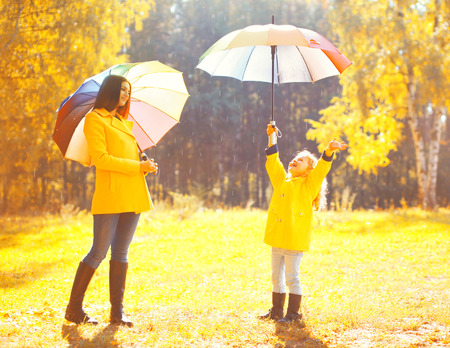 Moment of happiness! Happy family with umbrellas in sunny autumn rainy day, young mother and child in jacket outdoors enjoying rain over yellow leaves background Banco de Imagens - 62343240