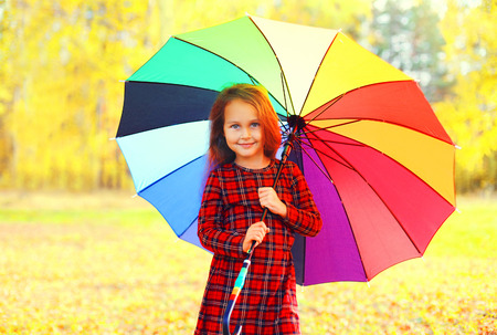 Happy smiling little girl child with colorful umbrella in sunny autumn day