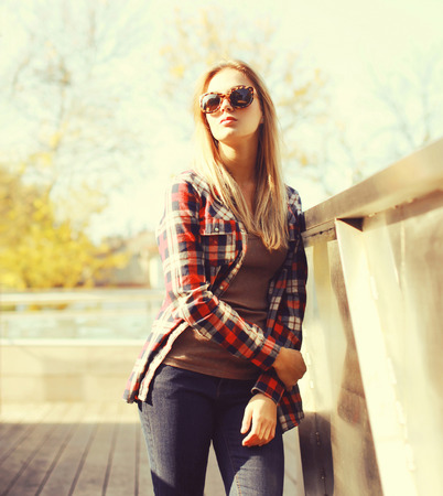 Fashion pretty woman wearing a sunglasses and checkered shirt in the city