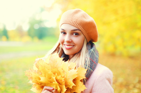 Portrait beautiful smiling woman with yellow maple leafs in warm sunny autumn day