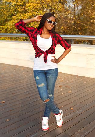 rastas: Hermosa mujer africana sonriente llevaba una gafas de sol, rojo camisa a cuadros de noche que presenta