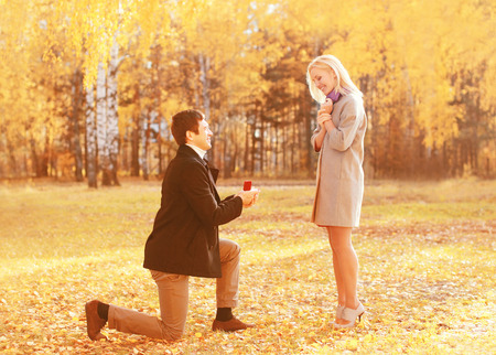 proposes: kneeled man proposes a woman to marry red box ring happy young romantic couple Stock Photo