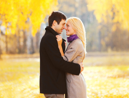 Portrait romantic smiling couple in love at warm sunny day over yellow leafs background