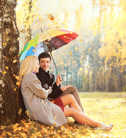 Happy loving young couple sitting under tree with colorful umbrella in warm sunny day falling leaves