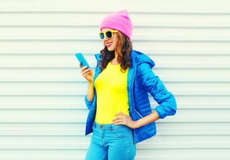 Mode fille cool cool souriant à l'aide de smartphone dans des vêtements colorés sur fond blanc portant un chapeau rose jaune lunettes de soleil et veste bleue Banque d'images
