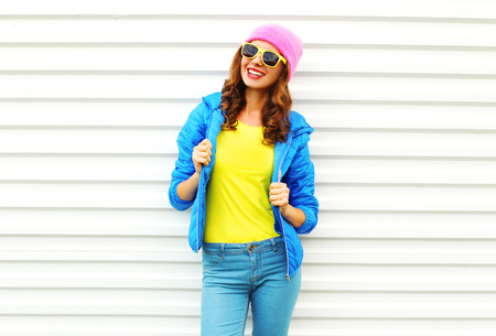 Fashion pretty smiling woman model in colorful clothes posing over white background wearing a pink hat yellow sunglasses and blue jacket