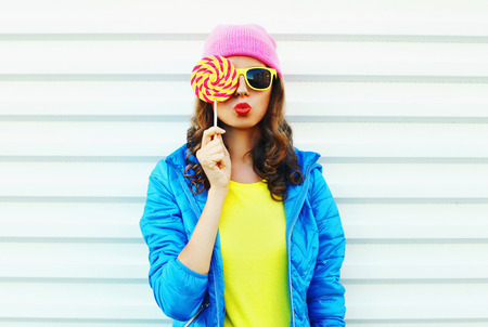 Portrait fashion pretty cool woman with lollipop in colorful clothes over white background wearing a pink hat yellow sunglasses and blue jacket