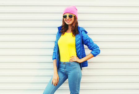 autumn color: Portrait fashion pretty smiling woman model in colorful clothes posing over white background wearing a pink hat yellow sunglasses and blue jacket Stock Photo
