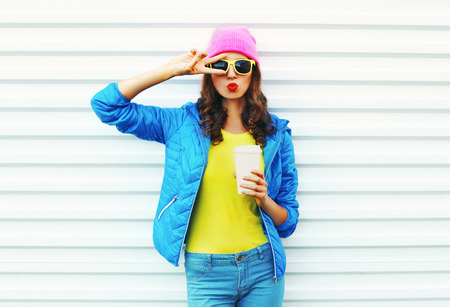 autumn young: Fashion pretty woman with coffee cup in colorful clothes over white background wearing a pink hat yellow sunglasses blue jacket Stock Photo