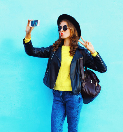 Fashion pretty cool young girl taking photo makes self portrait on smartphone wearing black rock style clothes over colorful blue background Stok Fotoğraf