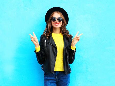 화려한 파란색 배경 위에 검은 바위 스타일을 입고 패션 꽤 웃고 멋진 여자