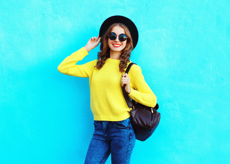 Fashion pretty smiling woman wearing a black hat yellow knitted sweater and backpack over colorful blue background Standard-Bild
