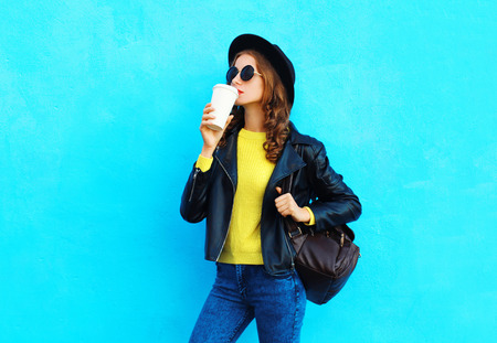 Fashion pretty young woman with coffee cup wearing a black rock style clothes over colorful blue background Stok Fotoğraf