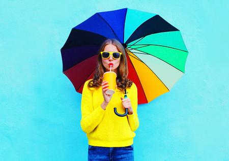 Arbeiten Sie hübsche Frau mit frischer Fruchtsaftschale und bunter Regenschirm am Herbsttag über dem blauen Hintergrund um, der eine gelbe gestrickte Strickjacke trägt Standard-Bild - 63469251