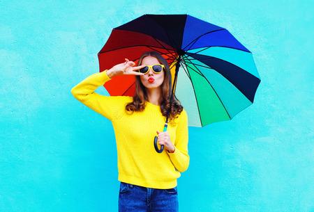 Moda donna piuttosto fresco azienda ombrello colorato nel giorno di autunno su sfondo blu che indossa un maglione maglia gialla