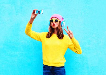 Mode fille cool dans les écouteurs en écoutant de la musique prise de photo rend autoportrait sur smartphone portant un vêtement coloré sur fond bleu