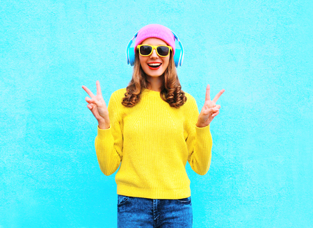 Fashion pretty cool smiling girl in headphones listening to music wearing a colorful pink hat yellow sunglasses and sweater over blue background Stok Fotoğraf - 64402545